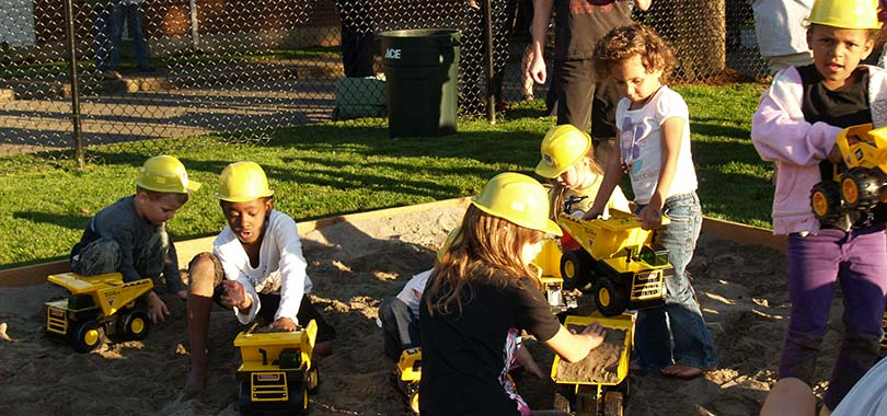 Kids with hardhats playing in sandbox